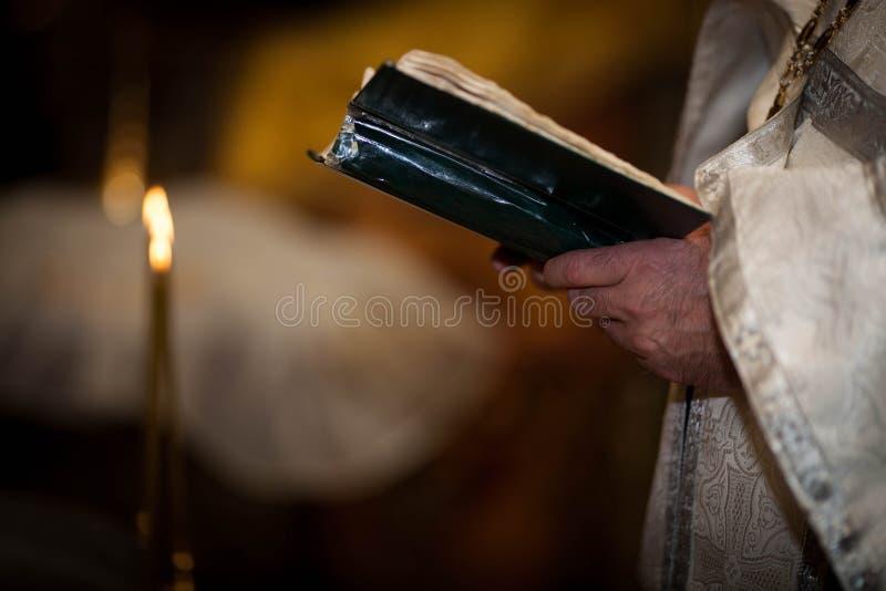 Der Priester hält die Bibel lizenzfreie stockbilder