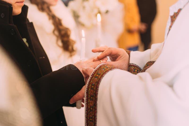 Der Priester kleidet einen Ring auf Finger, um sich während der kirchlichen Hochzeit zu pflegen stockbild