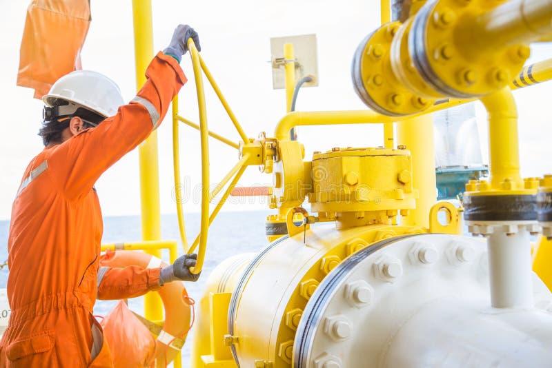 Der Produktionsbetreiber, der großes Kugelventil öffnet, um Gas zu erlauben, fließen Rohrleitung an der Offshoreöl- und Gasplattf lizenzfreie stockbilder