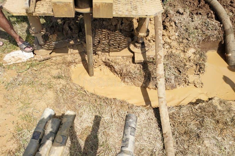 Der Prozess der Bohrung eines Lochs auf dem Wasser, Nahaufnahme, viel Schmutzwasser, Wasser mit Lehm stockbilder