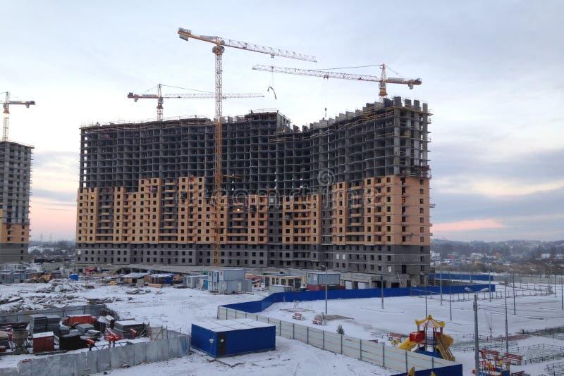 Der Prozess des Errichtens eines großen mehrstöckigen Wohngebäudes im Winter Die Arbeit von Baukränen Hälfte errichtetes Haus stockfotos