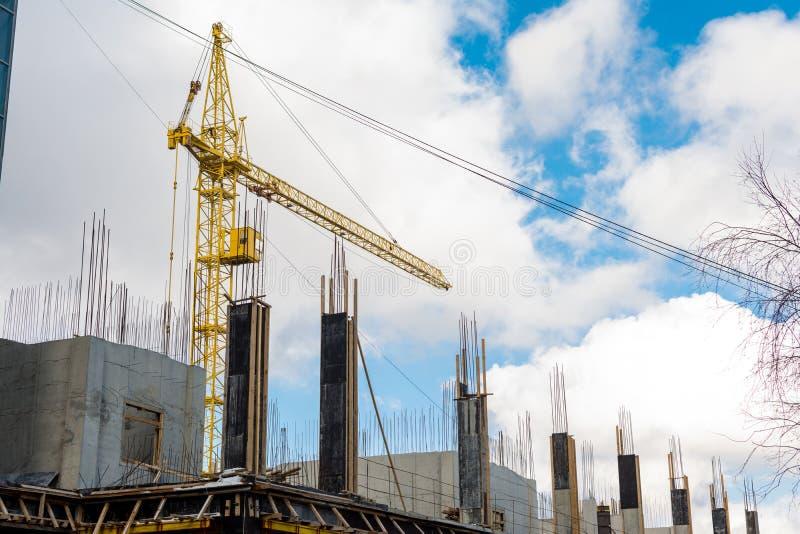 Der Prozess des Errichtens eines mehrstöckigen Wohngebäudes, ein gelber Turmkran, goss konkrete Spalten mit Installationen gegen  stockfoto