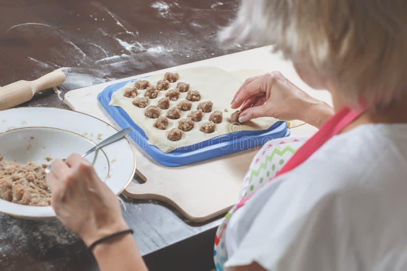 Der Prozess der Herstellung von köstlichen selbst gemachten Mehlklößen Frau legt das Fleisch, das auf den Teig füllt Ansicht von  lizenzfreie stockfotografie