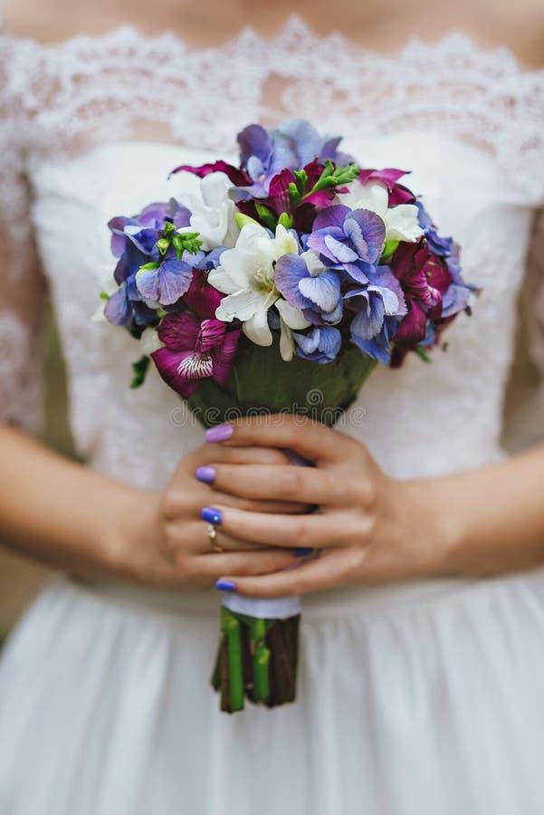 Der purpurrote Blumenstrauß der blauen und weißen Braut stockfotografie