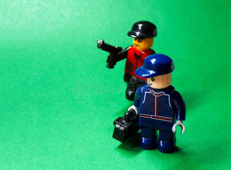 Der Räuber ist mit einer Waffe bewaffnet und jagt das Opfer mit einer Tasche lizenzfreies stockbild