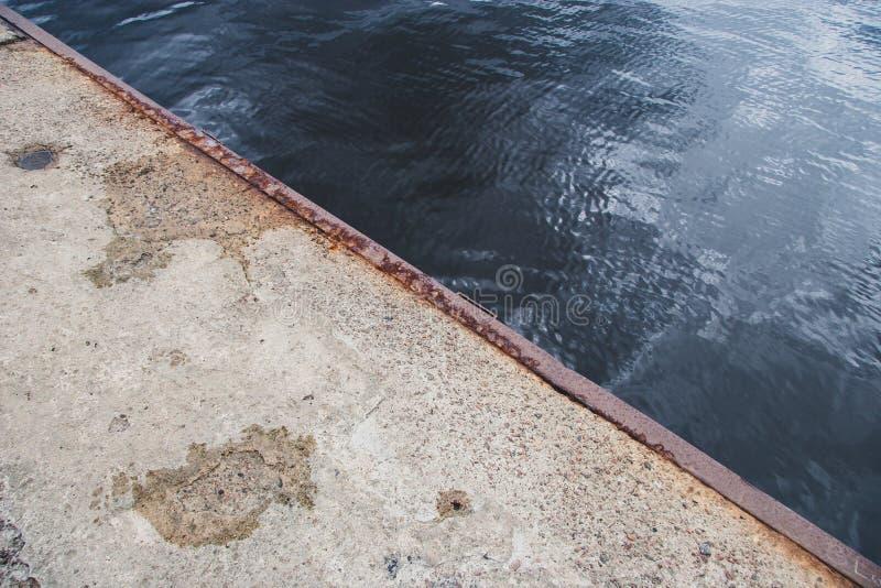 Der Rand des alten konkreten Piers mit einem rostigen Eisenrand lizenzfreies stockfoto