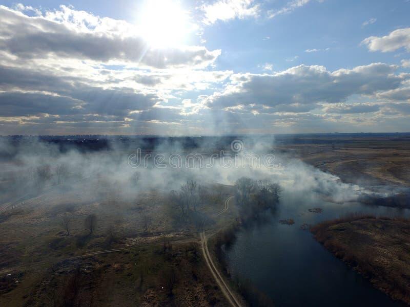 Der Rauch vom Brennen des Brummenbildes des trockenen Grases stockbilder