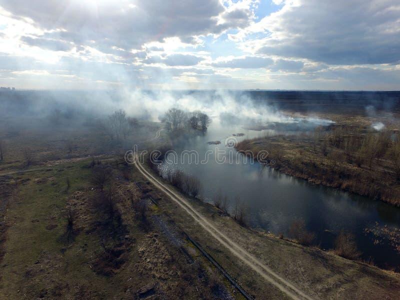 Der Rauch vom Brennen des Brummenbildes des trockenen Grases stockfotos