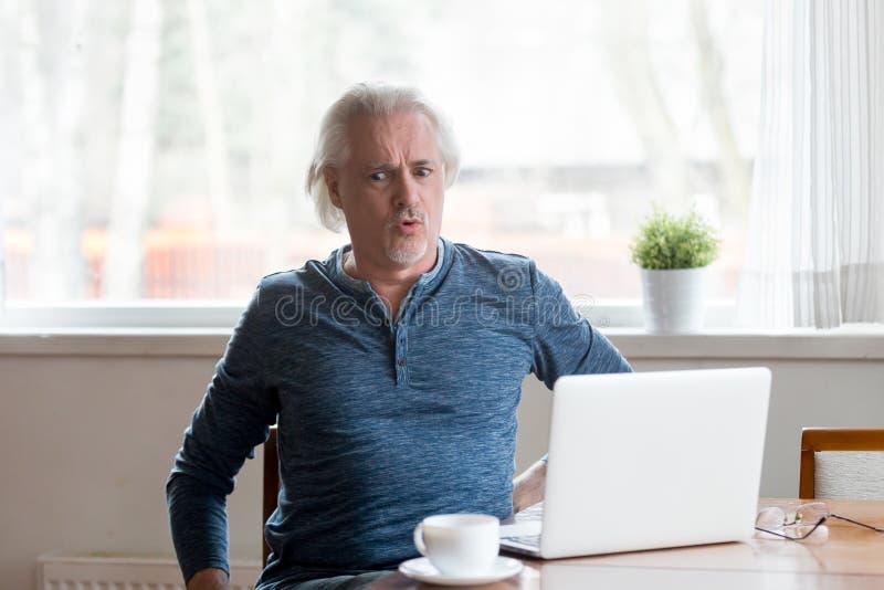 Der reife Mann, der an PC arbeitet, glaubt plötzlichen Rückenschmerzen stockbild