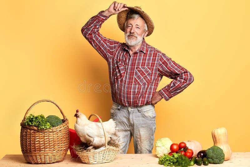 Der reife Mann, der seinen Strohhut, den ganzen Tag bearbeitet am Bauernhof entfernt, fühlt sich müde stockbilder
