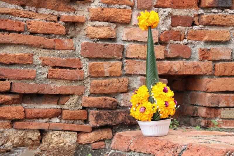 Der Reis, der vom Bananenblatt anbieten und die gelbe Ringelblume blühen auf dem Ziegelstein stockbild