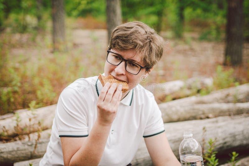 Der Reisende hielt an, um sich zu entspannen und ein Sandwich in einem Waldgebiet zu essen Wanderer, die zu Mittag Toast im Wald  stockbilder