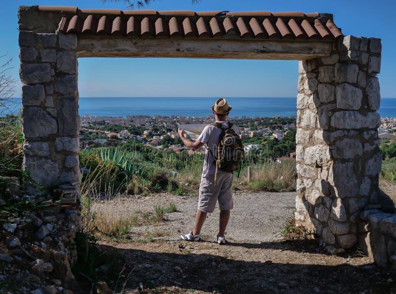 Der Reisendkerl steht mit einer Karte der Bereichsstände in einem zerstörten Steintor, hintere Ansicht lizenzfreies stockfoto