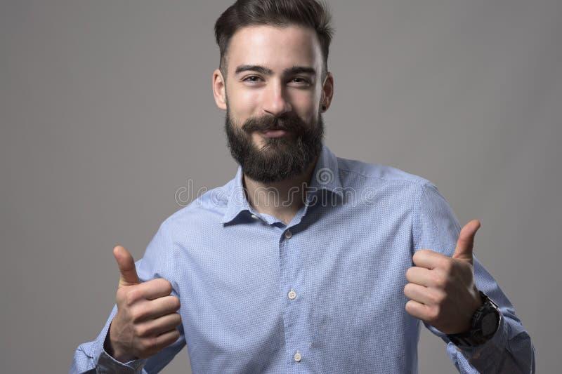 Der reizend glückliche junge bärtige intelligente zufällige Mann, der Daumen zeigt, up das Handzeichen, das an der Kamera lächelt stockfoto