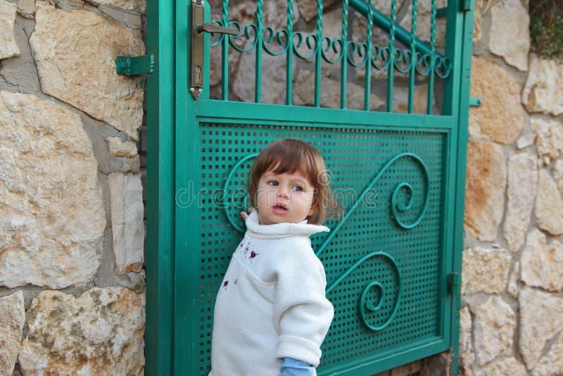 Der reizend Junge nahe zu Gartentor stockbilder
