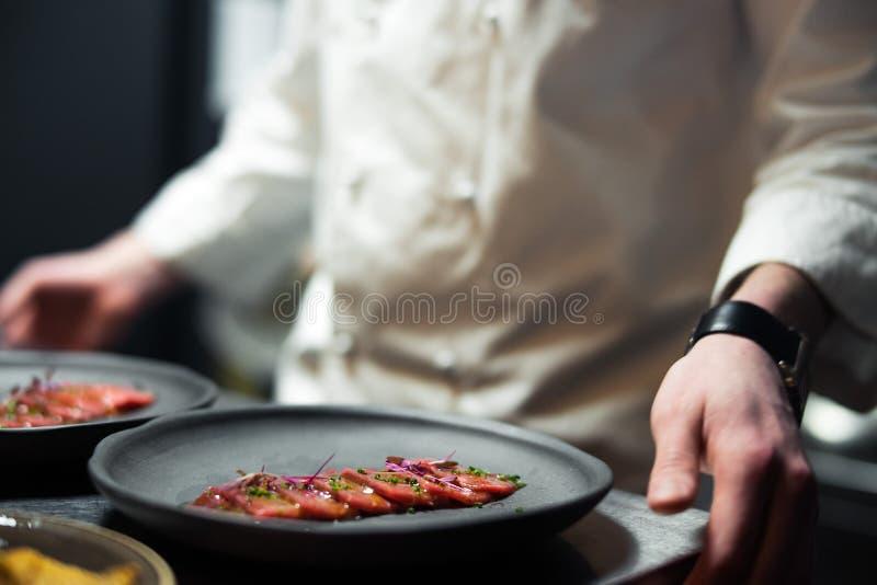 Der Restaurant-Chefkoch, der nahe bei grauer Platte mit Thunfisch steht, streifte Leiste und Grün stockfotografie