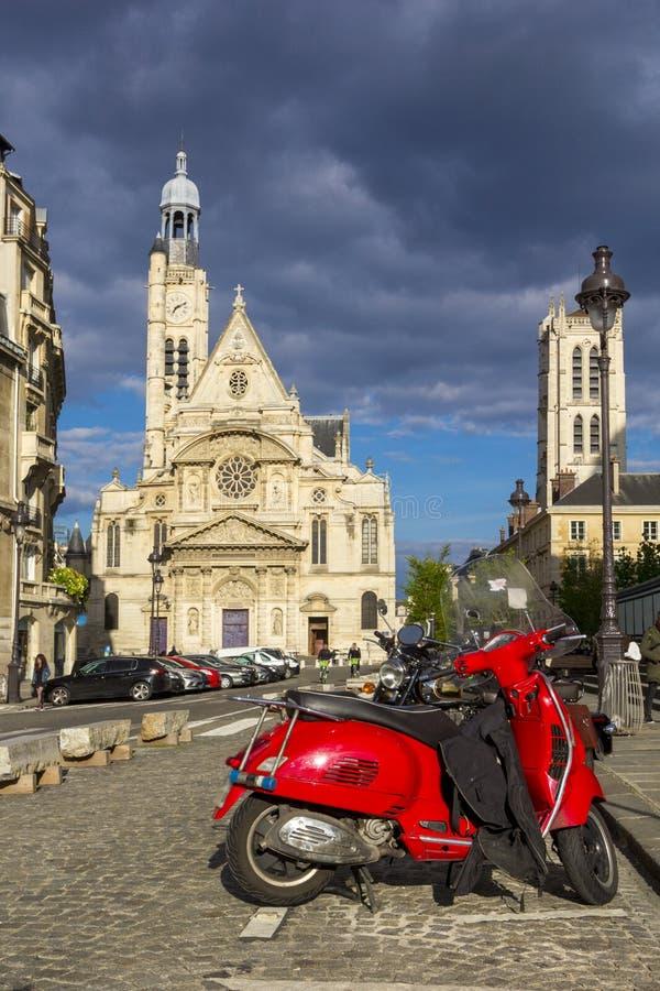 Der Retro- rote Roller, der in der Straße nahe Heilig-Etienne-DU-Mont geparkt wird, ist Kirche, Paris Frankreich stockbild