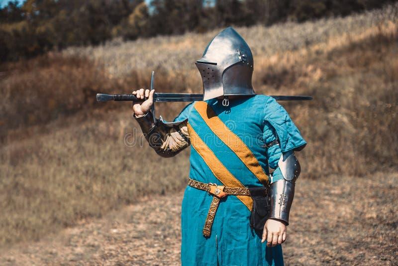 Der Ritter in der Rüstung, die eine Klinge halten steht lizenzfreie stockfotos