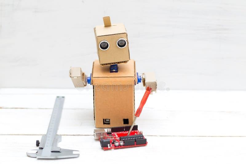 Der Roboter hält einen roten Schraubenzieher und eine Leiterplatte herein stockbilder