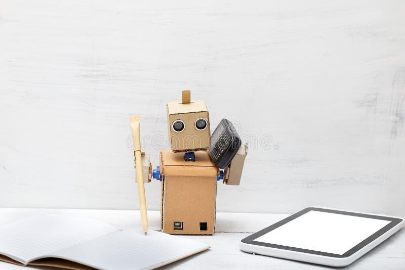 Der Roboter hält einen Stift und das Telefon ist naher Laptop arbeit lizenzfreie stockfotografie