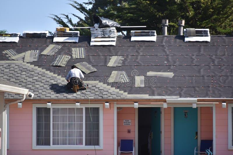 Der Roofer, der die Dachplatten an einem Rosa ersetzt, färbte Motel lizenzfreie stockbilder