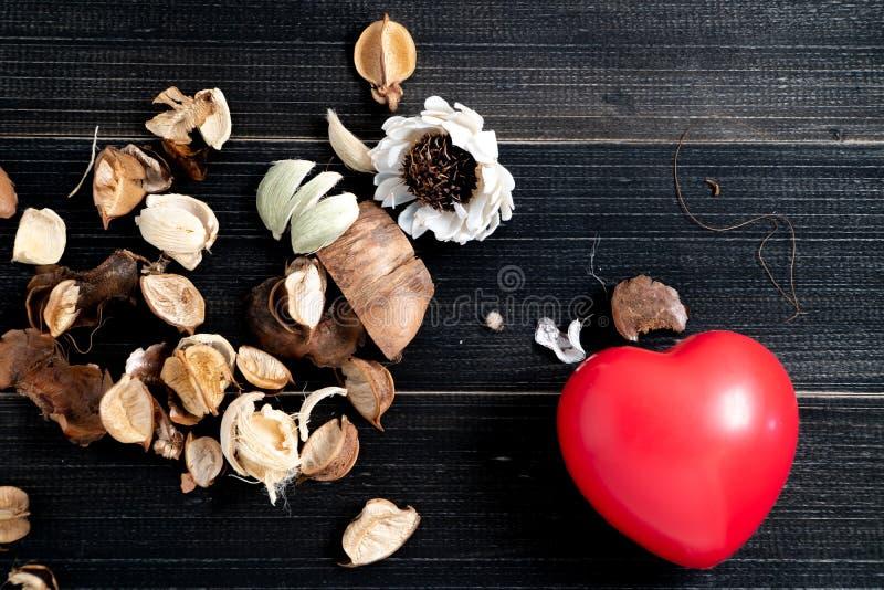 Der rote Herz Whit trocknete Blätter und Blume wird auf der linken Seite der schwarzen hölzernen Tabelle gesetzt Konzept der Lieb lizenzfreie stockfotografie