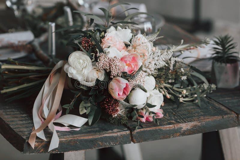 Der rustikale Blumenstrauß auf einem gealterten Holztisch gestaltungsarbeit lizenzfreies stockfoto