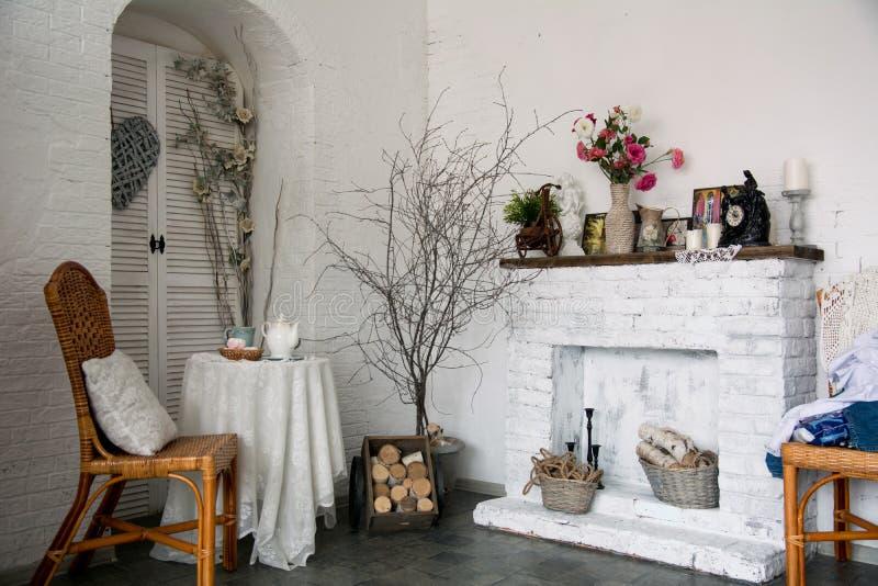 Der rustikale Innenraum des Designs mit einem Kamin, Blumen, Stuhl stockfotografie