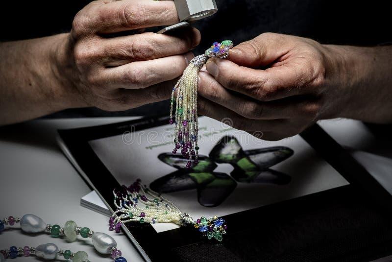 Der sachverständige Abschätzer des Schmucks betrachtet den Schmuck mit einer Lupe lizenzfreie stockbilder