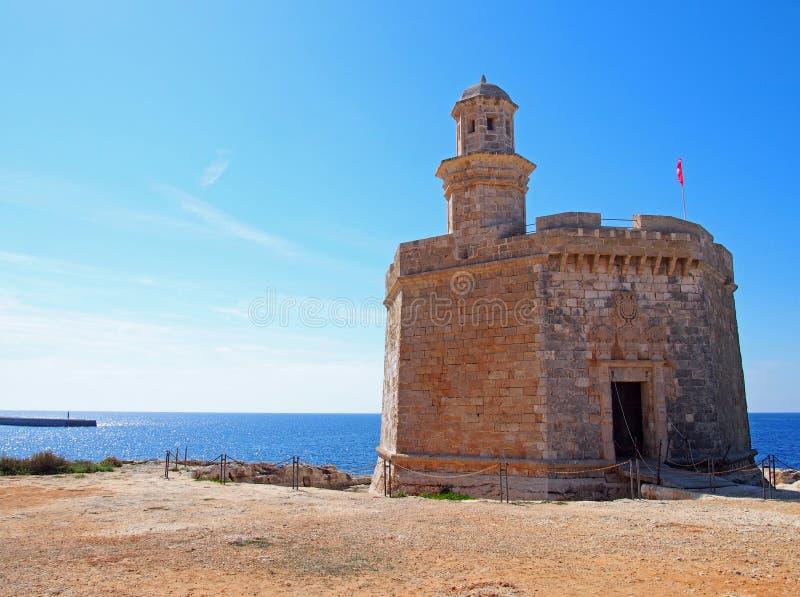 Der Sant Nicolau Castle in ciutadella menorca auf den Klippen mit blauem Sommermeer und blauem Himmel stockfoto