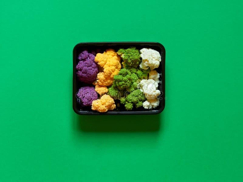 Der Satz bunter Blumenkohl violett, gelb, grün und Weiß boxte - in einer Plastikempfänger über einem grünen Hintergrund stockfotos