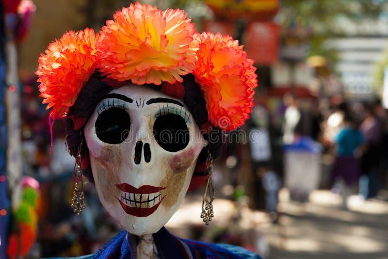 Der Schädel, der mit orange Papier-mache Blumen und Ohrringen/gemalt wurde und verziert war, verzierte Schädel für Dia de Los Mue stockfoto