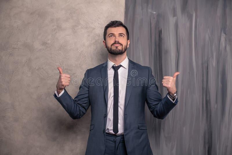 Der schöne hübsche Geschäftsmann steht in seinem Büro Finger auf die Seiten zeigend und oben schauend tragender Anzug und ein stockbilder