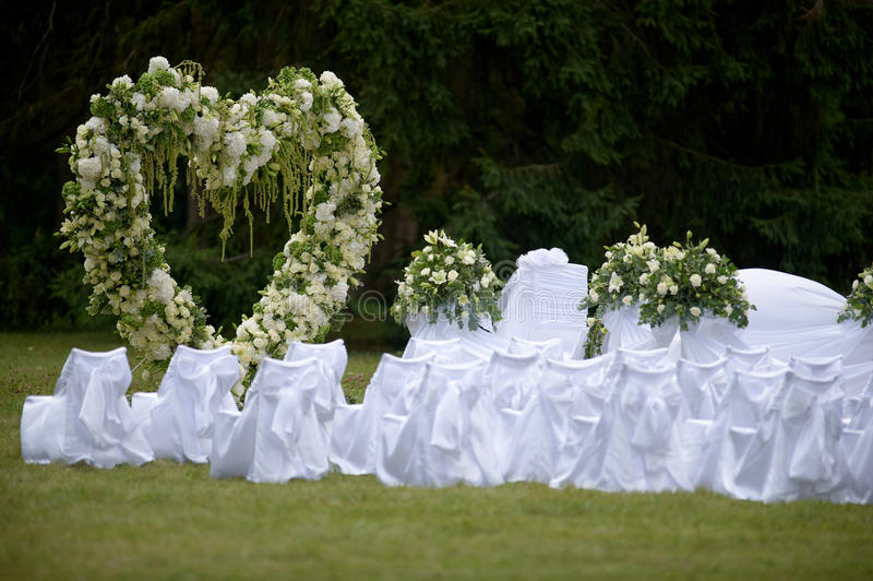 Der schöne Hochzeitsbogen, der mit Weiß verziert werden und das Grün fließen lizenzfreie stockfotos