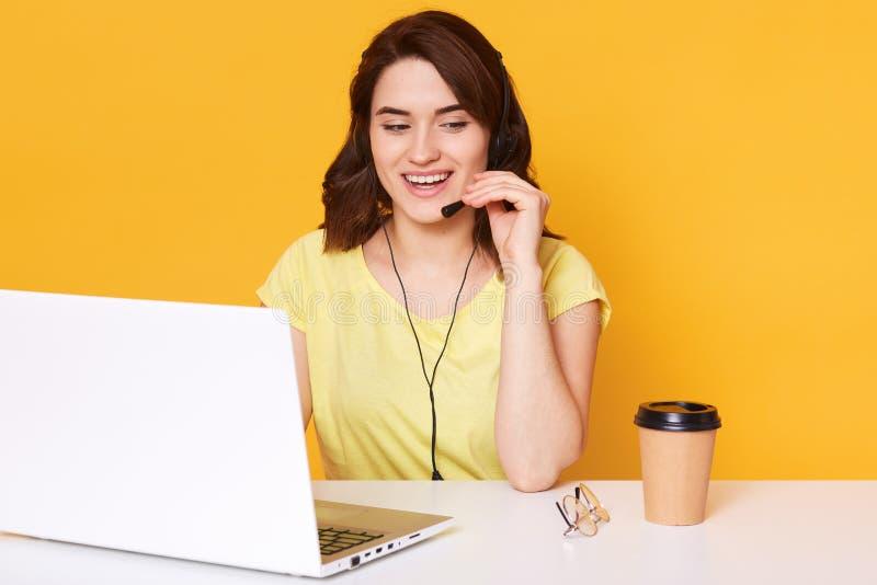 Der schöne junge Brunette, der in den Kopfhörern mit Mikrofon weiblich ist, sitzt am weißen Tisch mit Laptop und spricht mit dem  lizenzfreie stockfotos