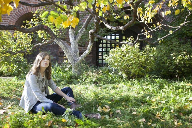 Der schöne junge Jugendliche, der auf einem Stamm eines Baums sitzt lizenzfreie stockbilder