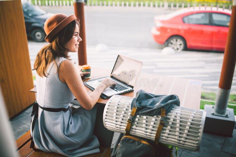 Der schöne junge kaukasische Welpe, der auf einer Terrasse in einem Café im Sommer an einem Holztisch in einem Hut und in einer P lizenzfreie stockfotos