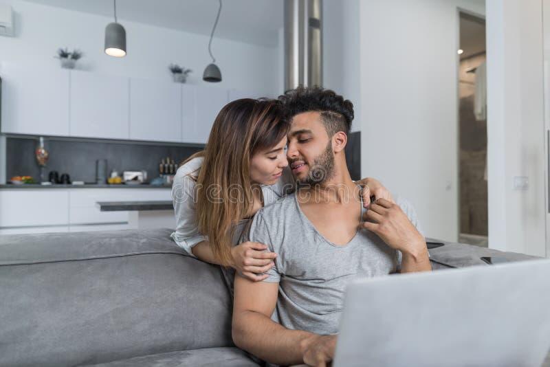 Der Schönheits-Kuss-Mann, der auf Couch mit Laptop-Computer in den moderne Wohnungs-jungen Paaren sitzt, verbringen Zeit zusammen lizenzfreie stockfotografie