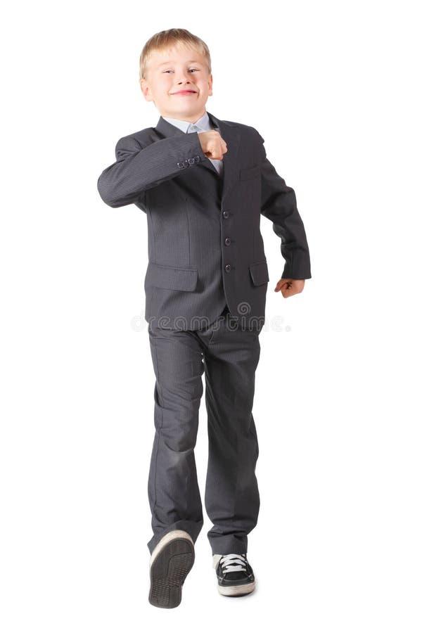 Der Schüler, der genauen Anzug trägt, geht lizenzfreie stockbilder