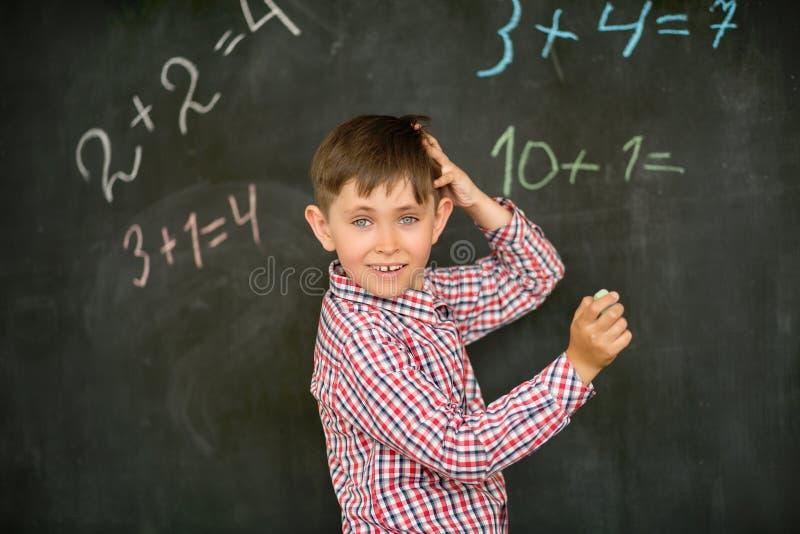 Der Schüler entscheidet auf dem Brett das Problem mit der Kreide und denkt über der Lösung, verkratzt seinen Kopf stockbild