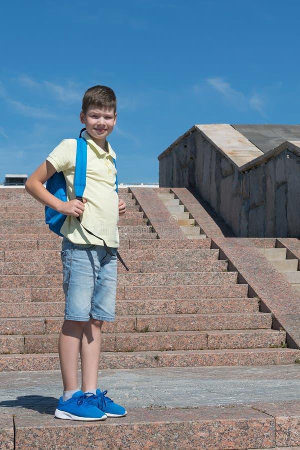 Der Schüler steht auf der Treppe mit einem blauen Rucksack für Schule lizenzfreies stockbild