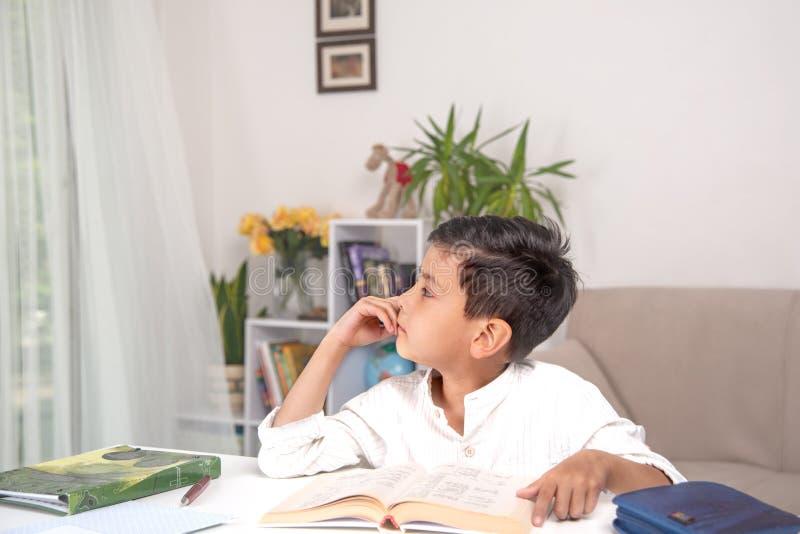 Der Sch?ler sitzt am Tisch zu Hause und tut seine Hausarbeit stockbilder