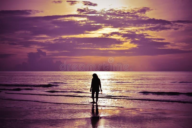 Der Schatten einer Frau, die auf den Strand bei Sonnenaufgang geht stockbild