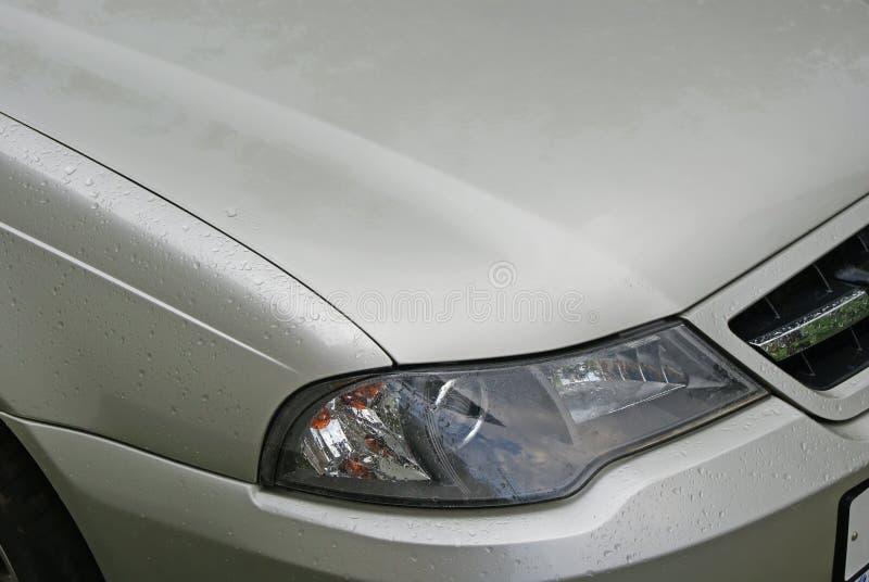 Der Scheinwerfer und die Haube des Autos Regentropfen auf dem Flügel des Autos lizenzfreies stockfoto