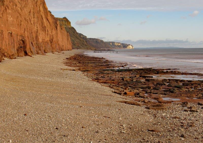 Der Schindelstrand bei Sidmouth in Devon mit den Klippen des roten Sandsteins der Juraküste im Hintergrund lizenzfreies stockfoto