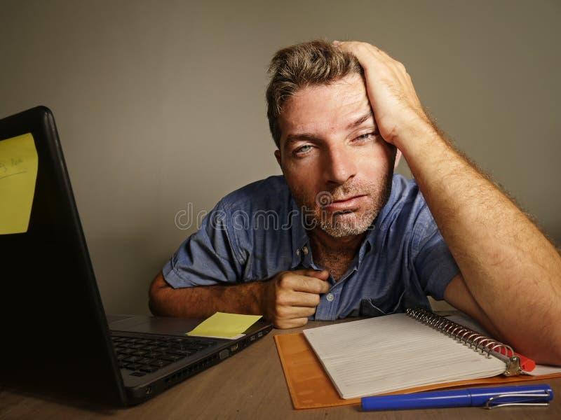 Der schläfrige müde und erschöpfte Mann, der an Laptop-Computer Buchhaltung nimmt Kenntnisse über Notizblock arbeitet, überbelast stockfotografie