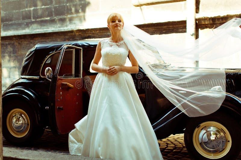 Der Schleier der Braut streute ein Retro- Auto aus, während sie hinter ihm steht lizenzfreies stockfoto