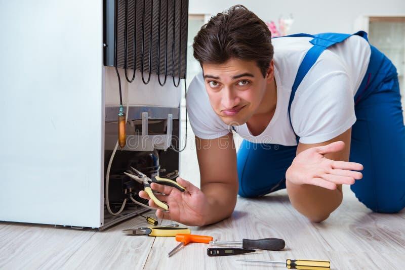 Der Schlosserauftragnehmer, der Kühlschrank im diy Konzept repariert stockfotografie