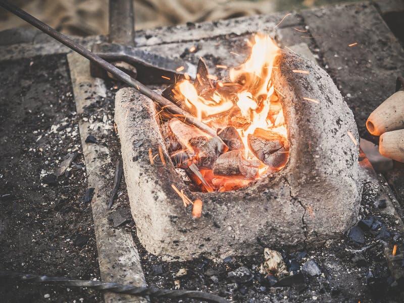Der Schmied hält das Billet über heißen Kohlen in einem Lehmofen Schmiedeheizungseisenmetallklingenherstellung stockfoto
