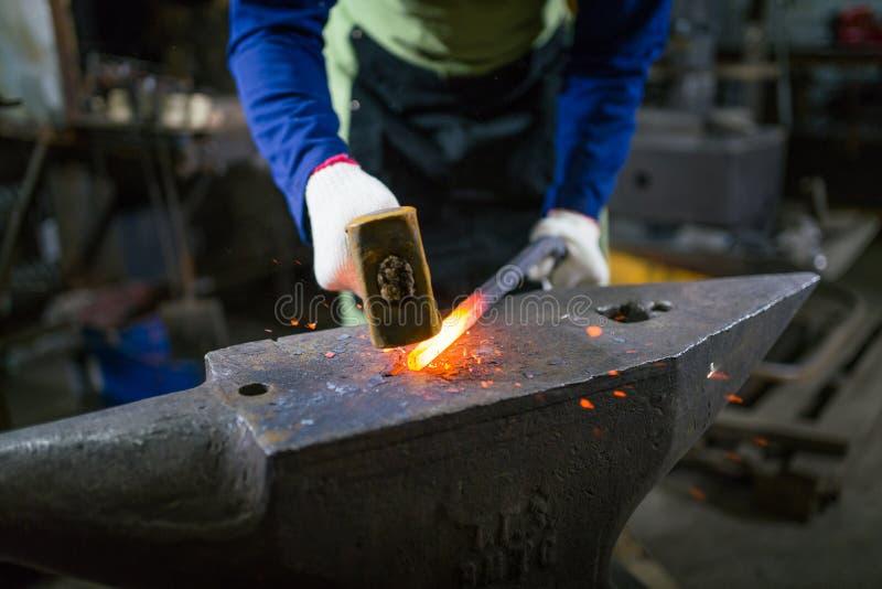 Der Schmied schmiedet das leuchtende Metall im Ofen, tritt heraus die Funken stockbild